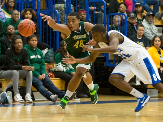 Crispus Attucks High School senior Darrell Hutchison (45) goes after the ball he knocked loose from Shortridge High School senior Deshawn Person (24) during first half action. Shortridge High School hosted Crisps Attucks High School in boys varsity basketball action, Wednesday, Nov. 26, 2014.