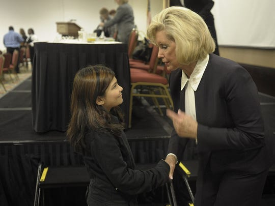 Lilly Ledbetter, whose fight for equal pay for women led to a federal law in her name, speaks with Lily Cedillo, 9, before addressing the Economic Summit for Women in Nashville, Tennesse, on Oct. 22, 2012.