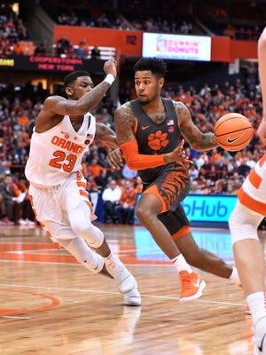 Clemson Tigers guard Shelton Mitchell  drives the ball as Syracuse Orange guard Frank Howard (23) defends Saturday afterenoon at the Carrier Dome in Syracuse, N.Y.