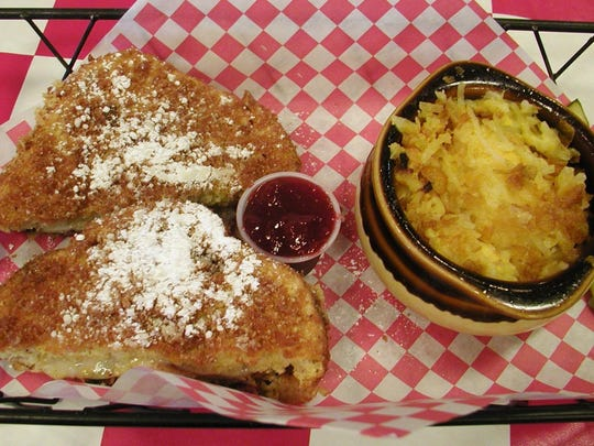 The Monte Cristo sandwich halves are served with a bowl of cheesy hash brown casserole.