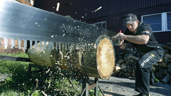World champion lumberjack Dave Jewett of Pittsford trains daily at the Pittsford Farms Dairy, in this case using a six-foot, four-inch saw.