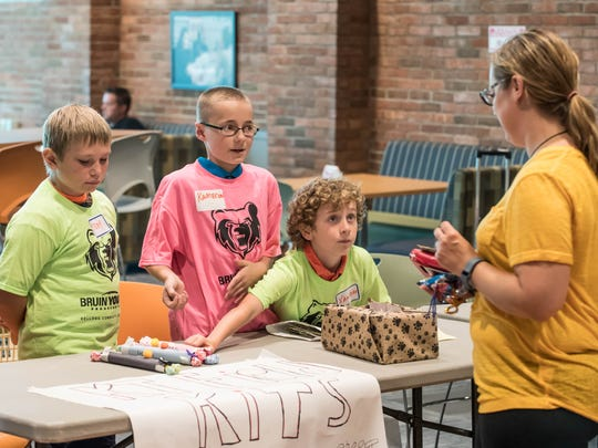 From left to right, Trey Willavize, Kameron Cooper and Xander Yoder sell candy to Sara Reed at a young entrepreneurs event at Kellogg Community College on Wednesday.