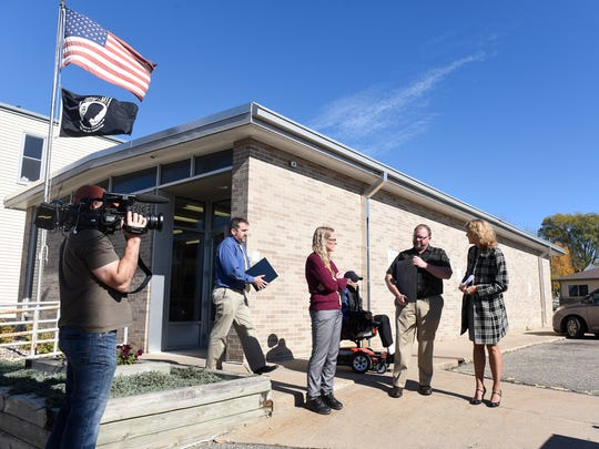 People gather for a dedication ceremony for a plaque in memory of Ivend Holen Tuesday, Oct. 18, in Kimball.