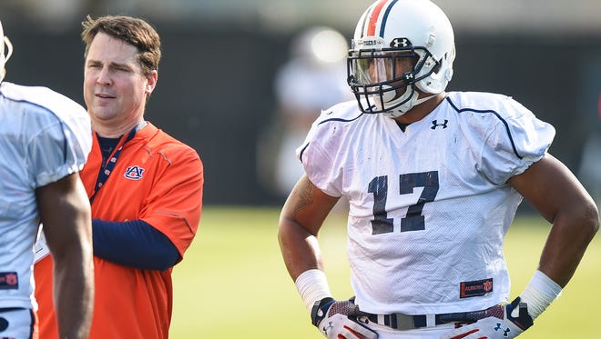 Auburn linebacker Kris Frost and defensive coordinator Will Muschamp observe practice.