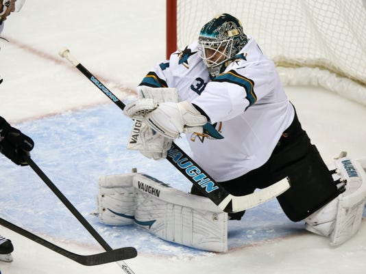 San Jose Sharks goalie Antti Niemi, right, of Finland, makes glove save off  a redirected shot from Colorado Avalanche left wing Jamie McGinn in the second period of an NHL hockey game in Denver on Tuesday, Oct. 28, 2014. (AP Photo/David Zalubowski)