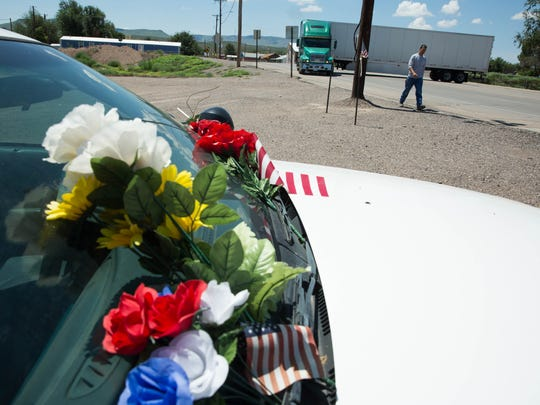 One year after Hatch Police Officer José Chavez, the police car parked on Franklin Street after a bank robbery unrelated to Chavez's death sits collecting flowers in remembrance of him. Pictured here Wednesday Aug. 9, 2017.
