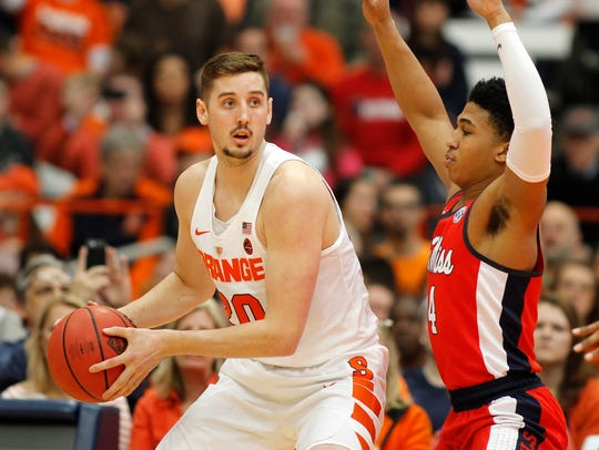 Syracuse's Tyler Lydon, left, looks to pass the ball