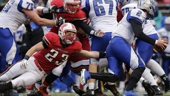 Waukesha West quarterback Conor Blount (2) beats a tackle by Homestead's Bradley Woldt (23) during the first   quarter of the Division 2 state championship in 2015. Both programs were once Division 1 powers but have become fairly regular entrants in the D2 playoffs today.