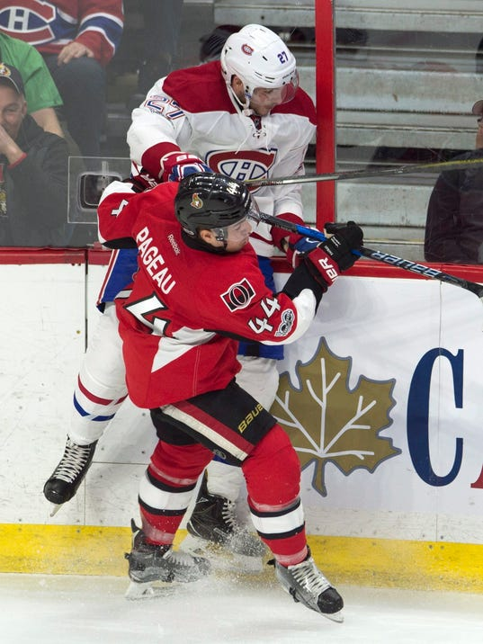 Ottawa Senators centre Jean-Gabriel Pageau (44) collides with Montreal Canadiens centre Alex Galchenyuk (27) along the boards during second-period NHL hockey game action in Ottawa, Ontario, Saturday, March 18, 2017. (Adrian Wyld/The Canadian Press via AP)