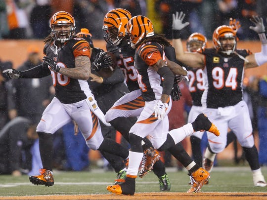 Bengals outside linebacker Vontaze Burfict (center) and the defense celebrate his interception in the fourth quarter of the playoff loss to the Steelers.