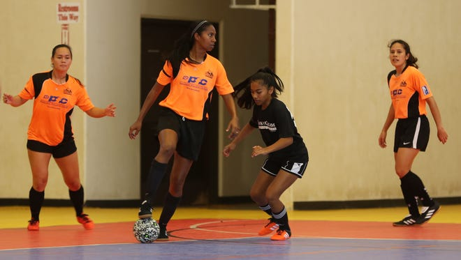 Personal Finance Center Lady Crushers' Simie Willter looks for options on the court as Bank of Guam Lady Strykers' Richelle Ragadio approaches her on defense in a Week 6 match of the Bud Light Women's Futsal League Sunday at the Guam Sports Complex gym. The Lady Crushers won 6-2.