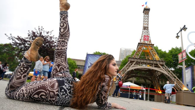 Nikki Palumbo, contortionist with the Carnival of Curiosity and Chaos, shows her flexibility while performing in front of the signature replica Eiffel Tower during Milwaukee's Bastille Days festival in 2017.