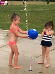(From left) Lilly Peters, 4, and April Proctor, 3, have fun with a ball and a steady stream of water.
