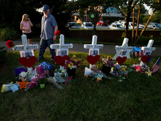 Capital Gazette reporter E.B. Furgurson III looks at crosses representing his five colleagues at a makeshift memorial at the scene outside the office building housing The Capital Gazette newspaper in Annapolis, Md., on July 1, 2018.