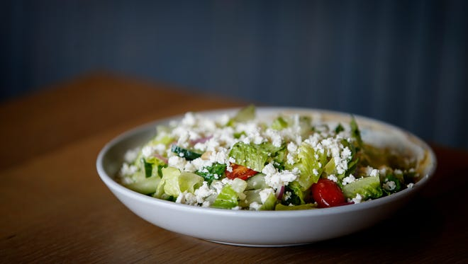 Greek Salad with tomatoes, cucumber, onion, olives, feta along with hummus and tzatziki smeared on the side, topped with a oregano dressing at tNext Door American Eatery located at 1350 Concourse Ave., Suite 165.