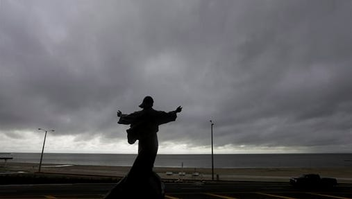 """A statue of Jesus calming the sea titled """"It is I"""" faces the bay and gulf, today in Corpus Christi, Texas, as Tropical Storm Bill begins to make landfall. The National Hurricane Center in Miami says Tropical Storm Bill came ashore this morning in the area of Matagorda County, about 90 miles southwest of Houston."""