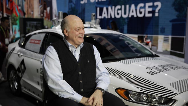 Ford CEO James Hackett smiles while getting ready for an interview next to a self-driving delivery vehicle at CES International Tuesday.