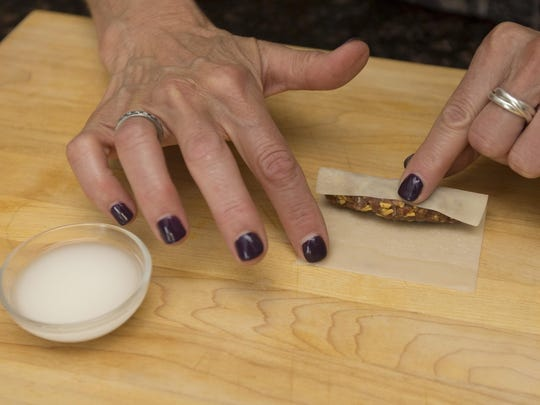 Robin Miller rolls up taquitos and seals them with a cornstarch-water mixture.