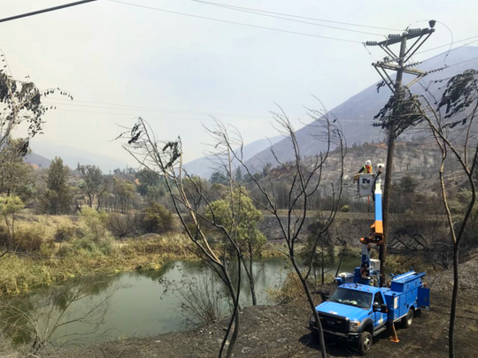 A Pacific Gas and Electric crew makes repairs Tuesday where the Carr Fire has burned.
