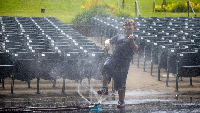 Jack Youngblood jams on his air guitar on the Cuthbert Amphitheater stage as he's doused by a sprinkler during his Eugene Recreation Services camp. The Cuthbert was added to the camp sites the city is using this summer after concerts at the venue were canceled. [Andy Nelson/The Register-Guard] - registerguard.com