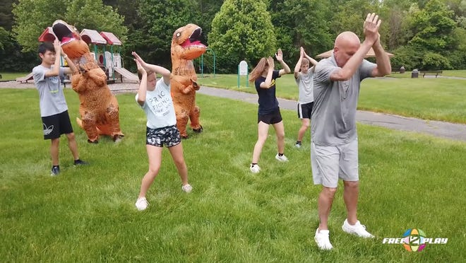 Gary Gray, local physical therapist and founder of the Gray Institute, dances with kids -- and a couple of dinosaurs -- during Free2Play Academy's live event celebration. Free2Play offered a free 30-day movement program for Lenawee County students during the month of May.
