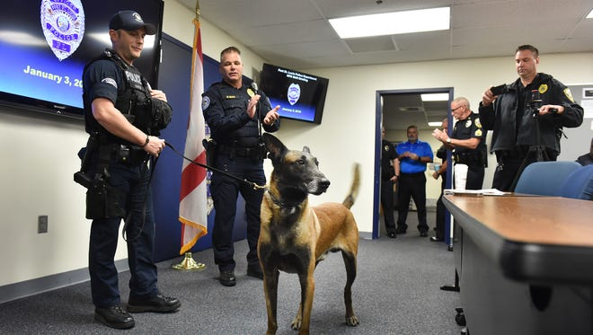 Port St. Lucie Police Master Sergeant Mike Beath (center) applauds Officer Will Harris (left) and his explosive ordinance detection K-9 partner Oliver after highlighting their accomplishments during Oliver's retirement from service announcement on Wednesday, Jan. 3, 2018, at the Port St. Lucie Police Department, 1201 SW Port St. Lucie Boulevard. To see more photos/video, go to TCPalm.com.