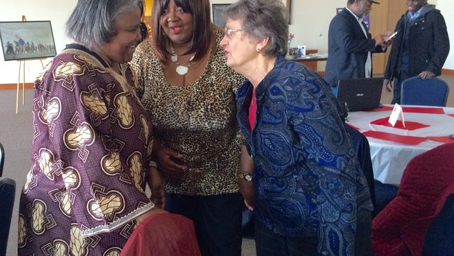 Mary Council-Austin, Jurosia Gipson and Sister Judith Schmidt share a greeting before the start of Ebony Vision's Black History Month potluck Saturday at Holy Family Catholic Church.