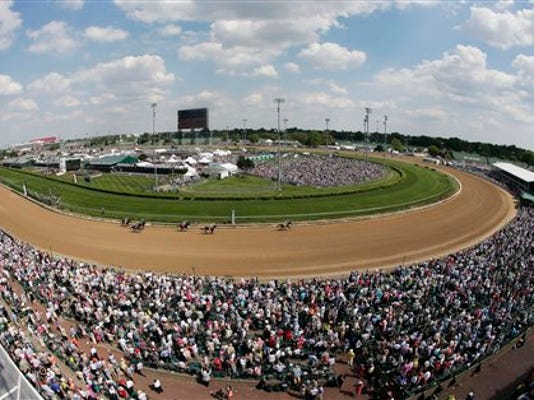 Fans watch a race before the 141st running of the Kentucky Derby horse race at Churchill Downs Saturday, May 2, 2015, in Louisville, Ky. (AP Photo/Charlie Riedel)