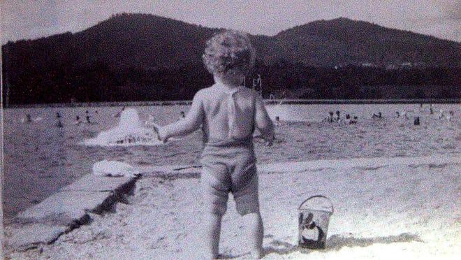 Nancy Baird Fortson, 2 years old, gazes from the Beaver Lake beach toward its swimming pool, circa 1940.