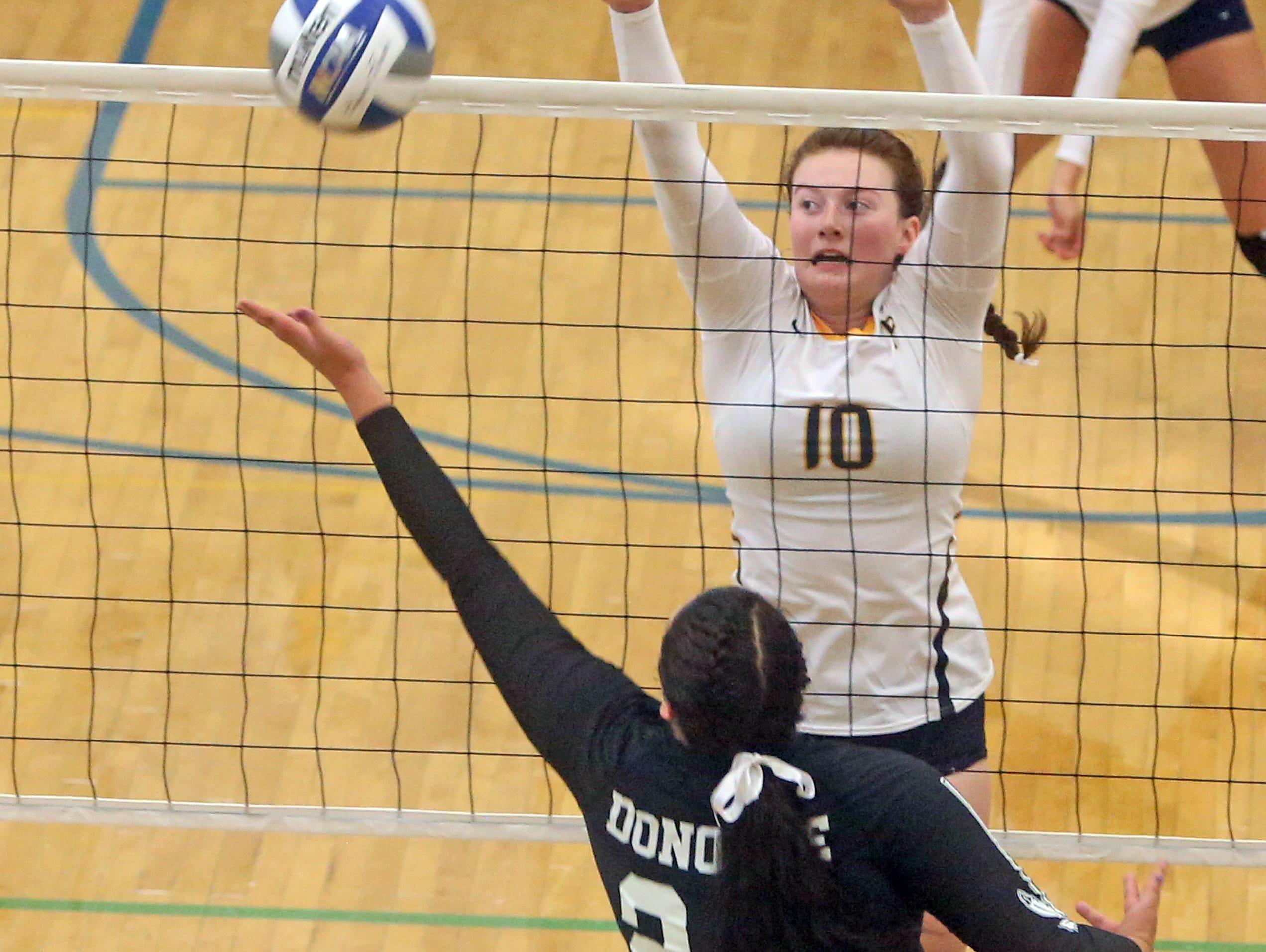 John Jay's Lauren Donohue reaches for a shot while Pelham's Alana Pettus defends during a varsity volleyball match at Pelham High School Sept. 3, 2015.