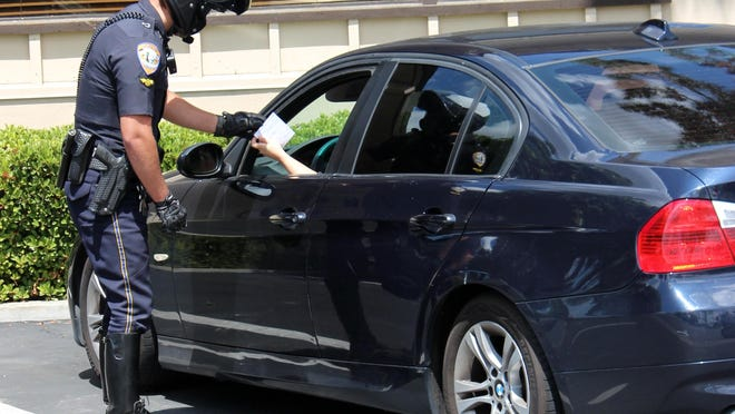 A Visalia Police Officer cites a motorist for texting while driving during a distracted driving detail.