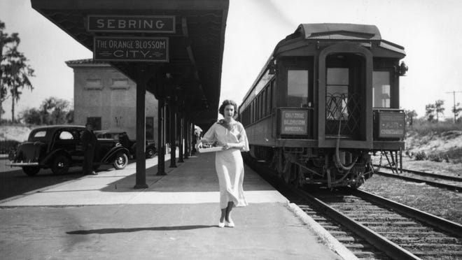 """A young woman stands near """"the Orange Blossom Special"""" train at railroad depot - Sebring, Florida."""