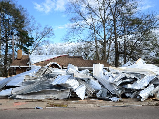 A pile of metal sits in front of a home as volunteers