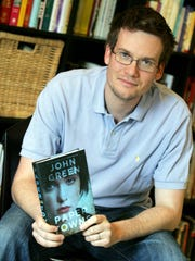 "John Green poses with a hardcover copy of ""Paper Towns"" in Indianapolis in 2009."