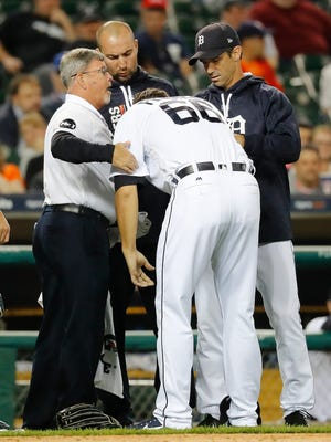 Detroit Tigers relief pitcher Jeff Ferrell bends over at the waist while heading to the dugout  with trainers and manager Brad Ausmus, right, after being hit by a line drive by the Oakland Athletics' Ryon Healy.