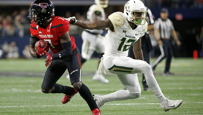 Texas Tech defensive back Jah'Shawn Johnson (7) intercepts a pass as Baylor wide receiver Quan Jones (12) tries to stop him during a game at Cowboys Stadium in Arlington, Texas.