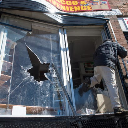 The owner of a Baltimore convenience store climbs into