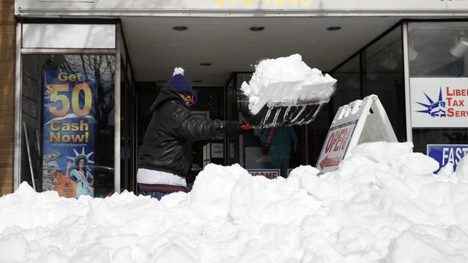 Jeff Williams widens the walking path in front of the storefront where he works in Patchogue, New York, Wednesday.
