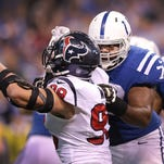 Indianapolis Colts tackle Gosder Cherilus (78) works on blocking Houston Texans defensive end J.J. Watt (99) in the second half of their game Sunday, December 14, 2014, afternoon at Lucas Oil Stadium.