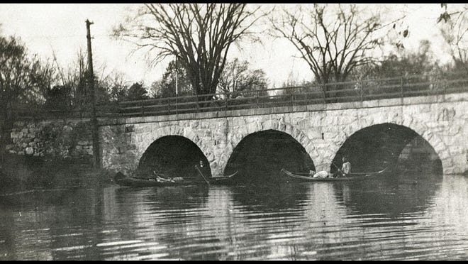 Canoeing under Cook's Bridge, circa 1905.  Although the haunted House is not visible (hidden behind the bridge in this view), the twin elms can be seen rising behind the bridge, and mark the house's location.