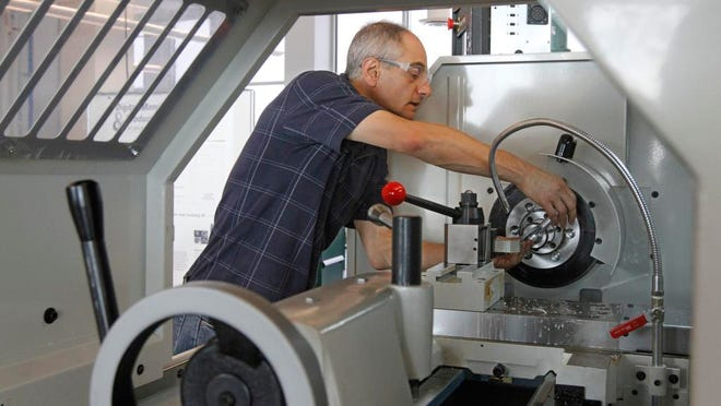 Domenic Maiola, Structures/Material Mechanical Technician at RIT, works at a lathe at RIT's new Digital Manufacturing and Product Realization Lab at Golisano Institute for Sustainability.