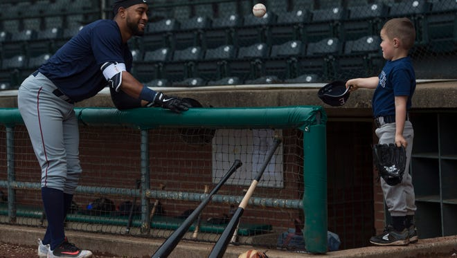 """Myles Babitt, left, tosses a ball to Gio Watson, 5, at the Evansville Otters spring training at Bosse Field Monday morning. """"G-Money. """"He's our team spirit,"""" Babitt said of the youngster. """"He hasn't bought into the nickname yet."""" Gio is the son of assistant coach Rob Watson."""