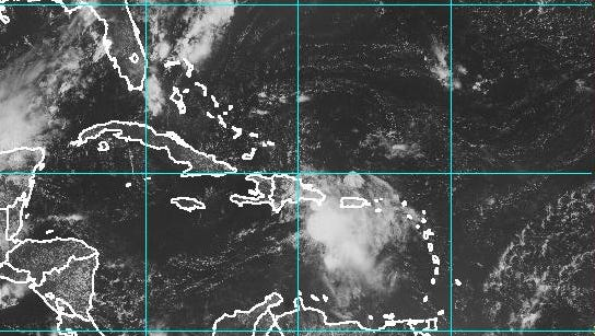 A satellite image of the Caribbean taken Friday morning shows Tropical Storm Erika (center right) spinning near Puerto Rico and the Dominican Republic.