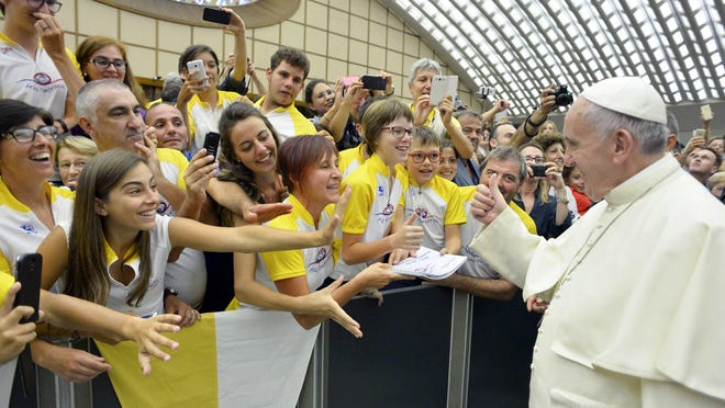 Pope Francis gives a thumbs-up to a group of young people during his weekly audience in Paul VI hall at the Vatican Wednesday.
