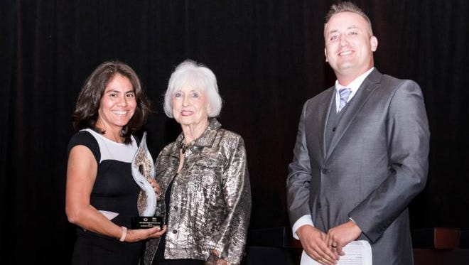 Linda Lundeen, center, receives the Top Hat award for Limited Service Hotel of the Year from the New Mexico Hospitality Association during the association's annual gala in Albuquerque.
