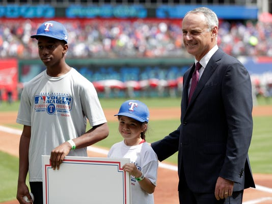 Texas Rangers MLB Youth Academy participants Benjamin King, left, and Aubrey Robledo, center, pose with baseball commissioner Rob Manfred, right, before the start of an opening day baseball game between the Houston Astros and Texas Rangers in Arlington, Texas, Thursday, March 29, 2018. (AP Photo/Tony Gutierrez)
