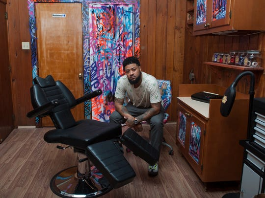 Angel Gutierrez, a Bronx native, sits in the back room of One Love Tattoo Studio & Art Gallery on Landis Avenue. Gutierrez will be the shop's lone tattoo artist.