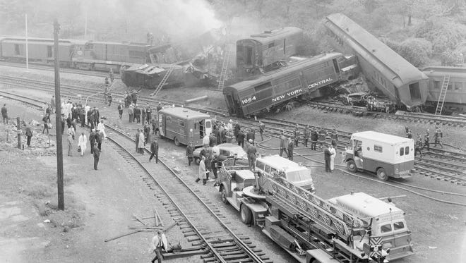 Firemen look at a tangled wreckage after two trains collided head-on in the New York Central railroad yards in upper Manhattan, May 22, 1967. At least seven people were killed it was reported. The collision occurred near West 148th Street, near Riverside Drive. The two three-unit engines smashed into each other on the northbound express track of the 130th Street yard. (AP Photo)