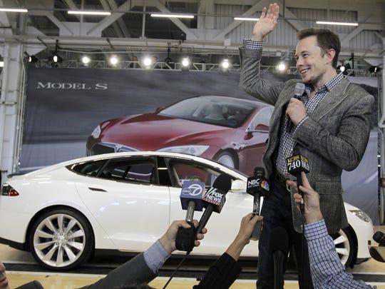 Tesla Motors CEO Elon Musk waves during a rally at