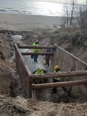 Workers repair a storm water main along Memorial Drive and Mariners Trail in Two Rivers.